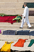 Indian man walks past laundry drying on the steps of Kali Ghat by the The Ganges River in City of Varanasi, Benares, India