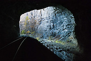 """At the unique Natural Tunnel State Park, near Duffield, Virginia, both a train and a river share the same natural limestone cave, measuring 850 feet (255 meters) long! The railroad has used this tunnel since 1890. Natural Tunnel began forming during the early Pleistocene Epoch and was fully formed by about one million years ago. The Glenita fault line running through the tunnel, combined with moving water and naturally forming carbonic acid may have formed Natural Tunnel through the surrounding limestone and dolomitic bedrock. After the tunnel formed and the regional water table lowered, Stock Creek diverted underground, then later took the path of least resistance through the Natural Tunnel, through Purchase Ridge, flowing south to join the Clinch River. Daniel Boone is believed to have been the first white man to see it. William Jennings Bryan (1860-1925) dubbed it the """"Eighth Wonder of the World""""; and the tunnel has been a tourist attraction for more than a century. Natural Tunnel State Park was created in 1967, and opened to the public in 1971. For a time, a passenger train line ran through Natural Tunnel, and today, the railroad still carries coal through it to the southeast USA."""