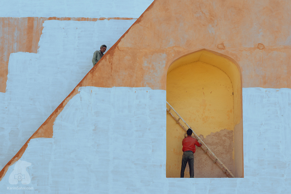 Two men repaint the walls of one of the Rashivalaya Yantra architectural astronomical instruments, at Jaipur's Jantar Mantar, an open-air observatory built by Maharaja Jai Singh II. Jantar Mantar consists of fourteen major geometric systems for measuring time, predicting eclipses and to probe the heavens.