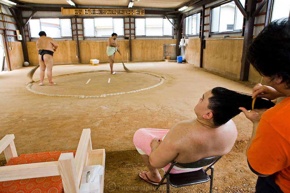 A member of the Professional Sumo Team (Musahigawa Beya) gets his hair fixed while others clean the practice ring in preparation for a tournament in Nagoya, Japan.
