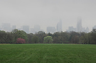 A misty midtown Manhattan skyline over the Great Lawn in Central Park