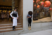 Young waiter emerges from the Louis Vuitton shop in London's Bond Street before a Vogue fashion festival.
