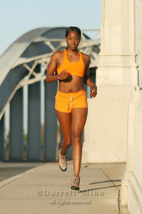 Model: LaKreshia Hart<br /> Orange running outfit.  Running on the sixth street bridge.<br /> <br /> Photo Credit Darrell Miho.<br /> &copy; Darrell Miho