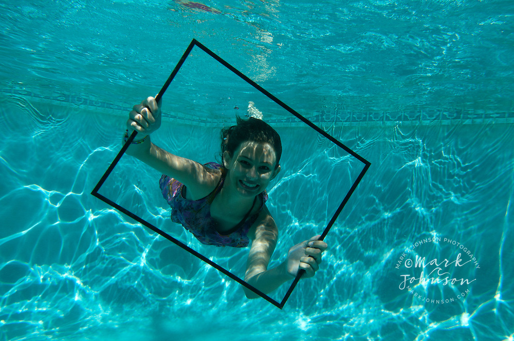Smiling teenage girl underwater in swimming pool, holding a picture frame