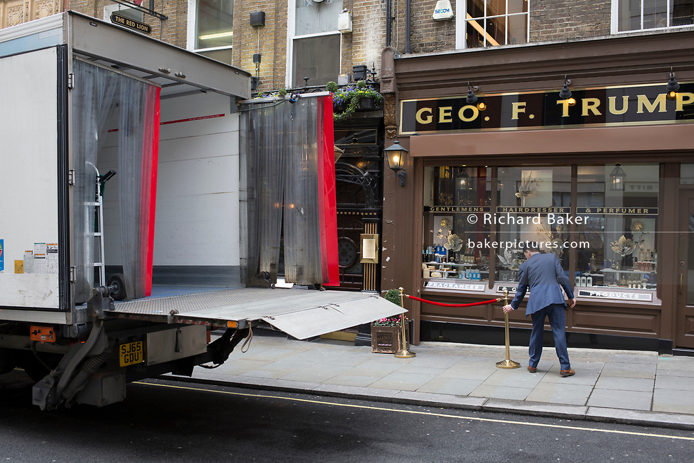 Alongside a delivery lorry that's parked at the kerbside, a man wearing a suit adjusts the rope barriers outside the gentlemens hairdressers and perfumer Geo. F. Trumper in their St. James's  shop on Duke of York Street, on 17th February 2020, in London, England.
