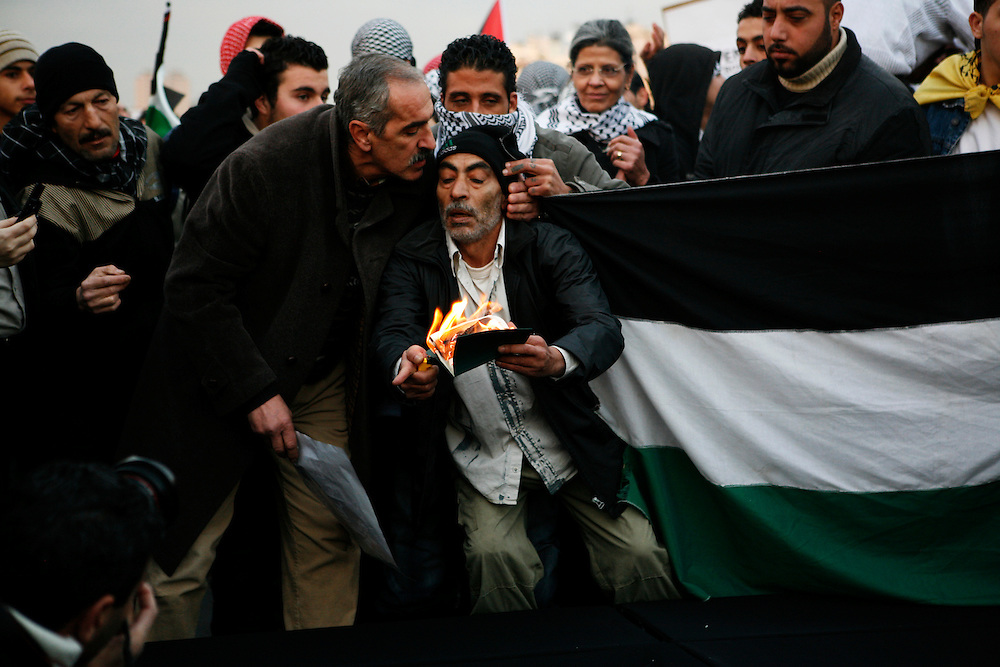 A Palestinian man with Egyptian papers burns them during a protest outside of the Egyptian embassy in Beirut to protest the country's complicity in the 2008-09 Israeli attacks on the Gaza Strip.