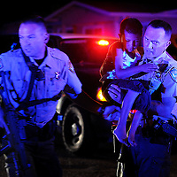 Yuba County Sheriff's deputies rush a young boy away from the scene on Maplehurst Avenue next to Brougham Way in Olivehurst just past midnight on Saturday, May 19, 2012. One man was shot and killed and a woman injured after a neighborhood dispute erupted in gunfire. (Nate Chute/Appeal-Democrat)