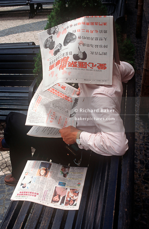 While still a Portuguese colony, a 1990s Macau gentleman reads his newspapers from under the pages of newsprint, on 10th August 1994, in Macau, China. (Photo by Richard Baker / In Pictures via Getty Images)