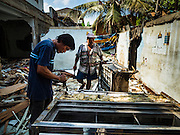 16 OCTOBER 2015 - BANGKOK, THAILAND:  Salvage dealers tear down a refrigerator case taken from a small shop in the Wat Kalayanamit neighborhood. The shop owner is being evicted. Fifty-four homes around Wat Kalayanamit, a historic Buddhist temple on the Chao Phraya River in the Thonburi section of Bangkok, are being razed and the residents evicted to make way for new development at the temple. The abbot of the temple said he was evicting the residents, who have lived on the temple grounds for generations, because their homes are unsafe and because he wants to improve the temple grounds. The evictions are a part of a Bangkok trend, especially along the Chao Phraya River and BTS light rail lines. Low income people are being evicted from their long time homes to make way for urban renewal.   PHOTO BY JACK KURTZ