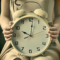 Young woman sitting and holding large alarm clock