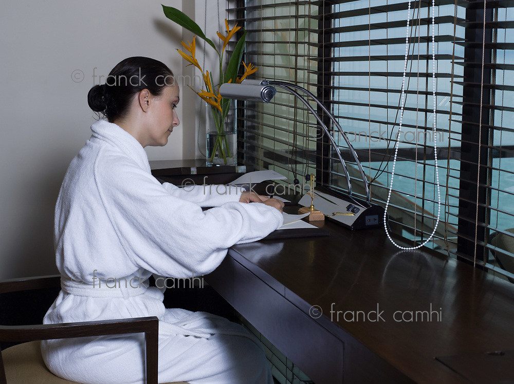beautiful calm and serene woman in palace hotel room writing a letter by a desk