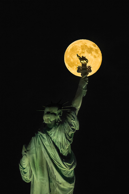 """Lighting Libertas"" Lady Liberty's torch is silhouetted by the Blue Moon on the last day of July 2015. When a full moon happens twice on one month, it is known as a blue moon. Shot with my Sigma 300mm at f/10 250th Second @ ISO 400 using my Nikon D800 on a Feisol 3371 tripod and a Feisol 50DC ballhead."