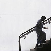 Sri Lanka, Silhouette of female worshipper carryling alms bowl at Buddhist shrine climbs sunlit stairs.