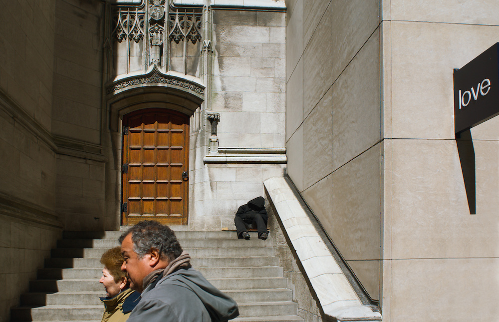 Couple passing homeless person on church steps