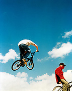 BMX rider catching some air while a biker below takes no notice, UK 2000's