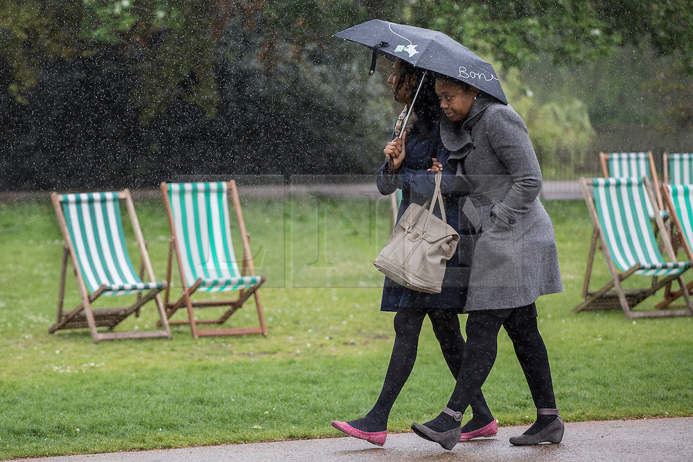 © licensed to London News Pictures. London, UK 09/05/2013. People walking under the rain in St James's Park in London on Thursday, 09 May 2013. Photo credit: Tolga Akmen/LNP