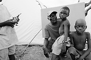 Pierre Omennis and his sons Charles McArthur, 8, and Esaie, 5, live in a tent camp on the main road near the airport. Pierre had picked his boys up from school and brought them home to their 3-story apartment building on the day the earthquake hit, like he would any other day. A few minutes later, he heard what he thought was a cannon being fired and the house collapsed. He couldn't see the boys and didn't know what to do except to start digging with his hands. First he found Charles, then his litle brother. It took another 15 minutes or digging and clawing with their hands to free him.