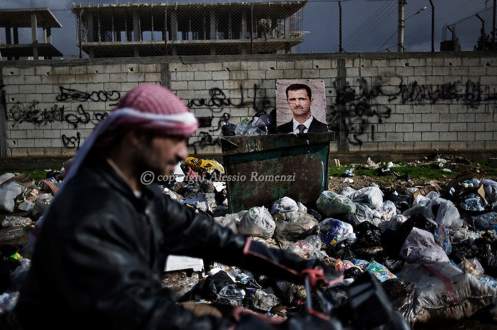 SYRIA - Al Qsair. A Syrian man drive a motorbike passing nearby a portait of Al Assad putted on rubbish in Al Qsair, on February 10, 2012. ALESSIO ROMENZI