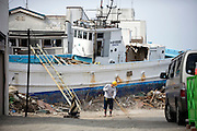 A man sweeps the road in front of a vessel that was washed ashore during the March 11 tsunamis in Ishinomaki City, Miyagi Prefecture, Japan on 26 May, 2011..Photographer: Robert Gilhooly