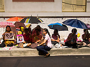 01 AUGUST 2013 - BANGKOK, THAILAND: People wait with umbrellas for shade from the midday sun in front of Siriraj Hospital, before Bhumibol Adulyadej, the King of Thailand, left the hospital Thursday. The King, 85, was discharged from Bangkok's Siriraj Hospital, where he has lived since September 2009. He traveled to his residence in the seaside town of Hua Hin, about two hours drive south of Bangkok, with his wife, 80-year-old Queen Sirikit, who has also been treated in the hospital for a year.   PHOTO BY JACK KURTZ