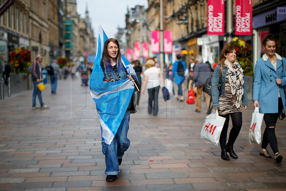 © Licensed to London News Pictures. 18/09/2014. Glasgow, UK. A man with Scottish Saltire flag walking in Glasgow city centre whilst people of Scotland going to polling stations to vote on the Scottish independence referendum on Thursday, 18 September 2014. Photo credit : Tolga Akmen/LNP