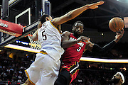 March 29, 2010; Cleveland, OH, USA; Miami Heat shooting guard Dwayne Wade (3) tries to make a shot over Cleveland Cavaliers center Ryan Hollins (5) during the first quarter at Quicken Loans Arena. Mandatory Credit: Jason Miller-US PRESSWIRE
