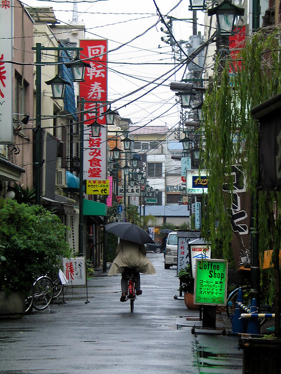 A shot of a person with an umbrella biking down a street in Tokyo.