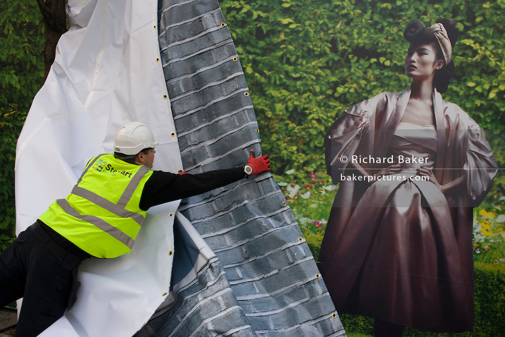A workman from Stewart Signs organises the hanging of a temporary printed media hanging outside a Dior shop being refurbished in central London.