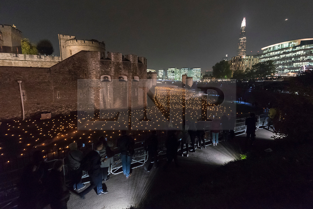 """© Licensed to London News Pictures. 05/11/2018. LONDON, UK.  Members of the public view a new installation by designer Tom Piper called """"Beyond the Deepening Shadow: The Tower Remembers"""", open at the Tower of London until Armistice Day 2018.  The moat is filled with thousands of individual flames commemorating the centenary of the end of the First World War.  Yeoman Warders, former servicemen and women, ceremonially lit the first flame followed by volunteers proceeding to light the rest of the installation, gradually creating a circle of light, radiating from the Tower.  Photo credit: Stephen Chung/LNP"""