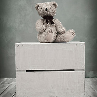 Small toy bear sat on the top of a box in a childrens playroom