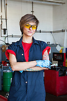 Portrait of a happy mechanic wearing protective gear with arms crossed in auto repair garage