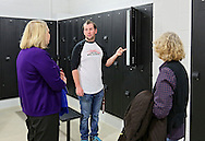Raymond Glueck (center), 18, senior on Linn-Mar swim team, answers questions in one of the locker rooms during the open house at the new Linn-Mar Aquatic Center in Marion on Thursday, November 14, 2013.