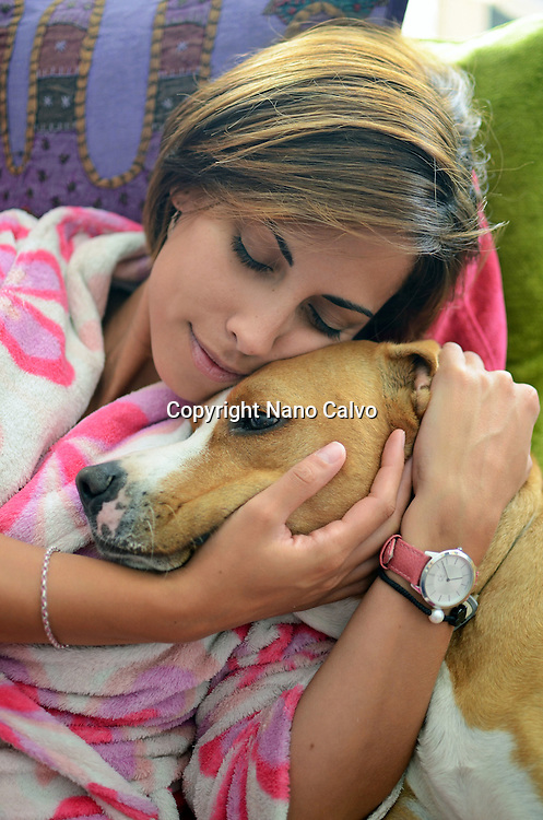 Young woman hugging her dog at home