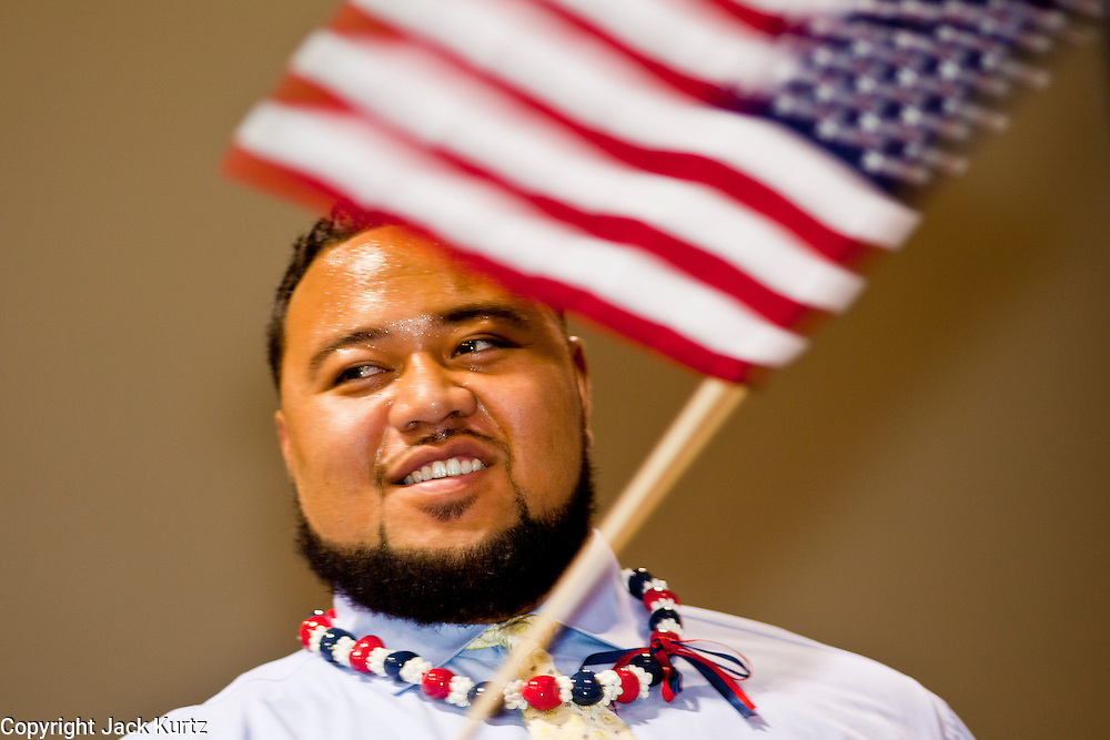 """July 2 - PHOENIX, AZ: Arizona Cardinals' offensive lineman TAITUSI """"Duece"""" LATUI,   originally from Tonga, waves an American flag while he is sworn as a US citizen Friday. Nearly 200 people were sworn in as US citizens during the """"Fiesta of Independence"""" at South Mountain Community College in Phoenix, AZ, Friday. The ceremony is an annual event on th 4th of July weekend and usually the largest naturalization ceremony of the year in the Phoenix area.  Photo by Jack Kurtz"""