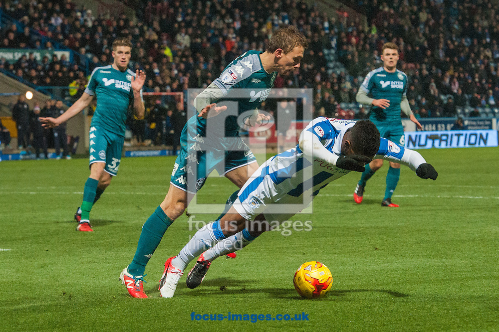 Elias Kachunga of Huddersfield Town goes down under a challenge from Stephen Warnock of Wigan Athletic during the Sky Bet Championship match at the John Smiths Stadium, Huddersfield<br /> Picture by Matt Wilkinson/Focus Images Ltd 07814 960751<br /> 28/11/2016