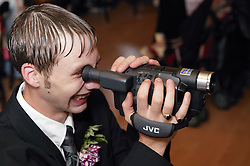 Guest using video camera at a wedding reception,