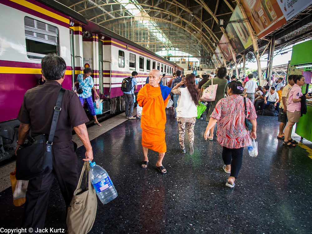 16 APRIL 2014 - BANGKOK, THAILAND:  A Buddhist monk going back to his temple walks to his train in Hua Lamphong Railway Station in Bangkok. Thai highways, trains and buses were packed Wednesday as Thais started returning home after the long Songkran break. Songkran is normally three days long but this year many Thais had at least an extra day off because the holiday started on Sunday, so many Thais started traveling on Friday of last week.   PHOTO BY JACK KURTZ