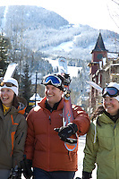 A group of skiers smile as they carry their skis while walking through Whistler Village on a sunny winter day.