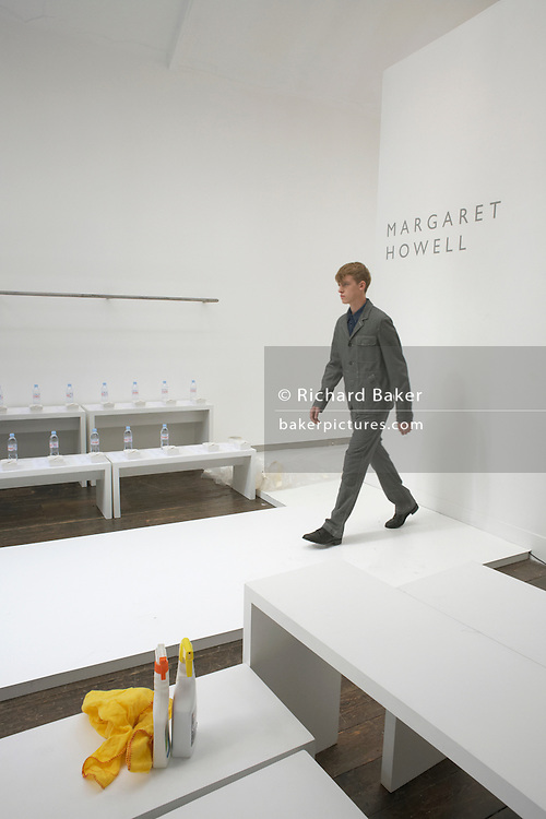 "A male model starts his walk on the catwalk of couturier Margaret Howell's Fashion Week show rehearsal in the company's retail flagship and design studio at 34 Wigmore Street, Central London England. With a duster and spray cleaning agent in the foreground, the young man walks, as if having emerged through the wall. Bottles of bottled mineral water await their users but the fashion show's audience have yet to arrive. Howell is one of Britain's more understated of couture brands alongside more flamboyant personalities. Howell admits to being ""inspired by the methods by which something is made .. enjoying the tactile quality of natural fabrics such as tweeds, linen and cotton in a relaxed, natural and lived in look."""