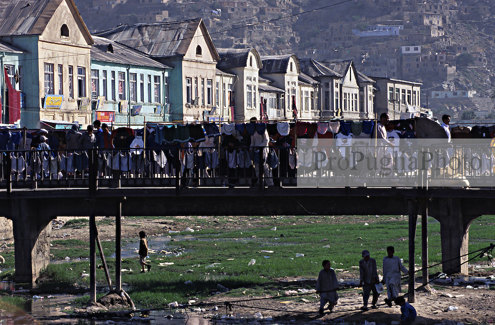 Kabul, children play in a greef field where a river used to flow, and street vendors sale underwear on the bridge.