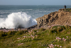 © Licensed to London News Pictures. 22/05/2020. Padstow, UK. A photographer takes photos of huge waves of up to 15ft hit the coastline at Harlyn bay and the surrounding coves of North Cornwall. There is currently no RNLI Lifeguard service in the county due to Coronavirus (Covid-19), potentially causing issues as an unusual combination of large swell and warm weather is expected during the upcoming bank holiday weekend. Photo credit : Tom Nicholson/LNP