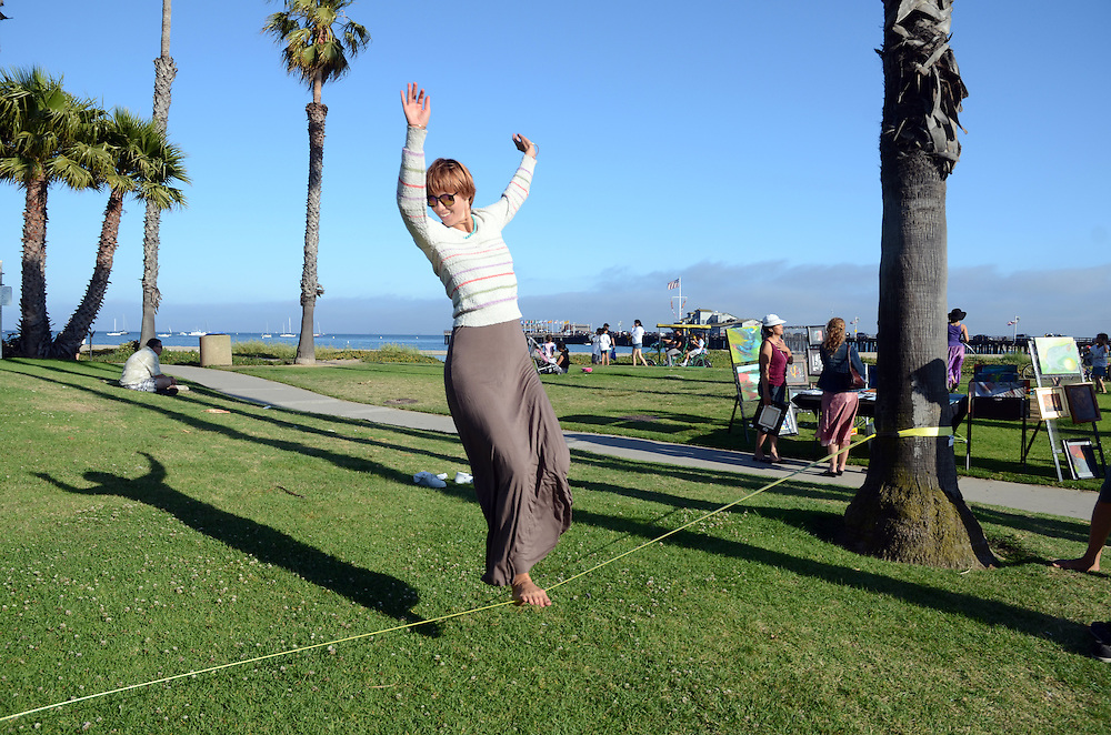 Young woman slacklining at Cabrillo Park in Santa Barbara, CA