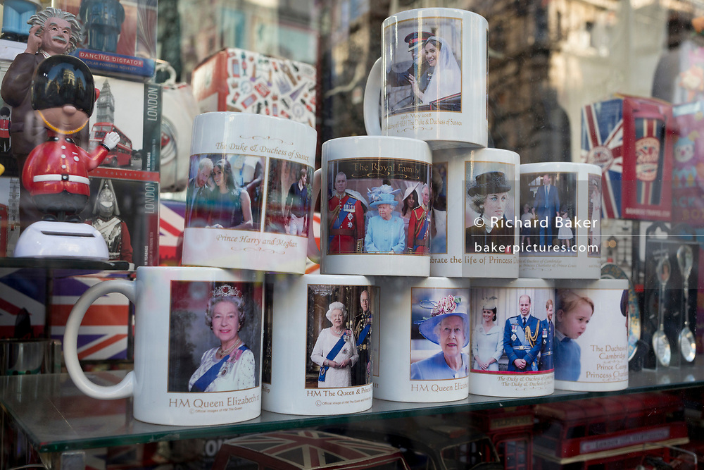 British royal family merchanidise and tourism souvenir mugs which show the faces of Queen Elizabeth, Diana the Princess of Wales and the Duke and the Duke Duchess of Sussex (Prince Harry and Meghan Markle) on their wedding day, on display in the window of trinket shop in Oxford Street, on 15th January 2020, in London, England.