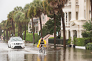Bicyclists makes way through floodwater along the Battery in the historic district as Hurricane Joaquin brings heavy rain, flooding and strong winds as it passes offshore October 4, 2015 in Charleston, South Carolina.