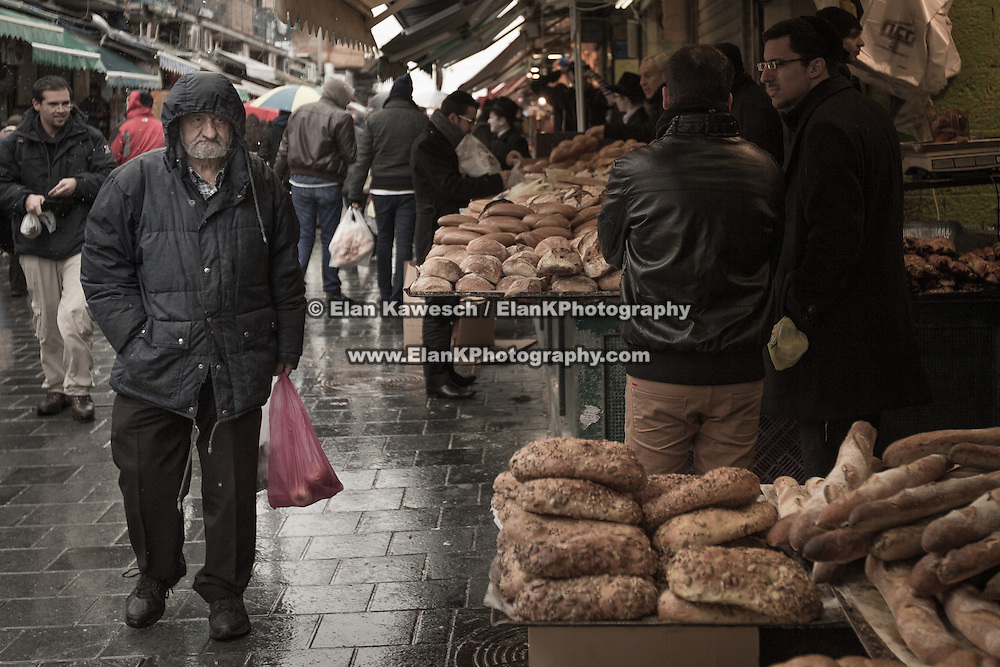 A man looks at a bread selection as rain falls at The Mahane Yehuda Shuk on January 9, 2015 in Jerusalem, Israel. (Photo by Elan Kawesch)