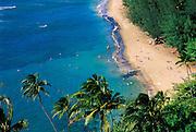 Sunbathers and blue Pacific waters at Ke'e Beach, Na Pali Coast, Island of Kauai, Hawaii