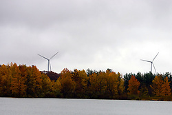 30 October 2009: windmills that are a part of the twin groves wind farm stand in the background of Dawson Lake inside of Moraine View State Park near LeRoy Illinois.  The trees that still retain leaves show the colors of autumn.