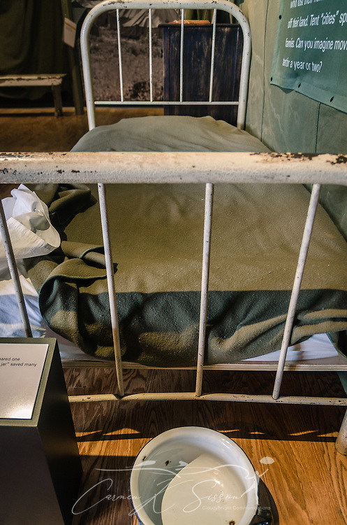 "A replica of an African-American ""Tent City"" bedroom is displayed at Lowndes Interpretive Center, Feb. 3, 2015, in Hayneville, Ala. After the passage of the 1965 Voting Rights Act, many black tenant farmers registered to vote and were kicked off their land by the weathy, white landowners. The chamber pot at the foot of the bed kept inhabitants from having to trek to the outhouse at night. (Photo by Carmen K. Sisson/Cloudybright)"