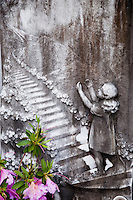 Ticino, Southern Switzerland. Touching tombstone relief of a little girl ascending to heaven.