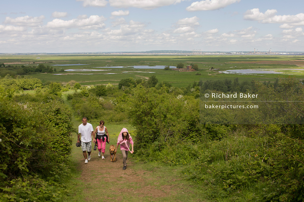 A family climb Northwood Hill with a wetland landscape below, an wildlife area near Halstow on the Kent Thames estuary marshes, potentially threatened by the future London airport.